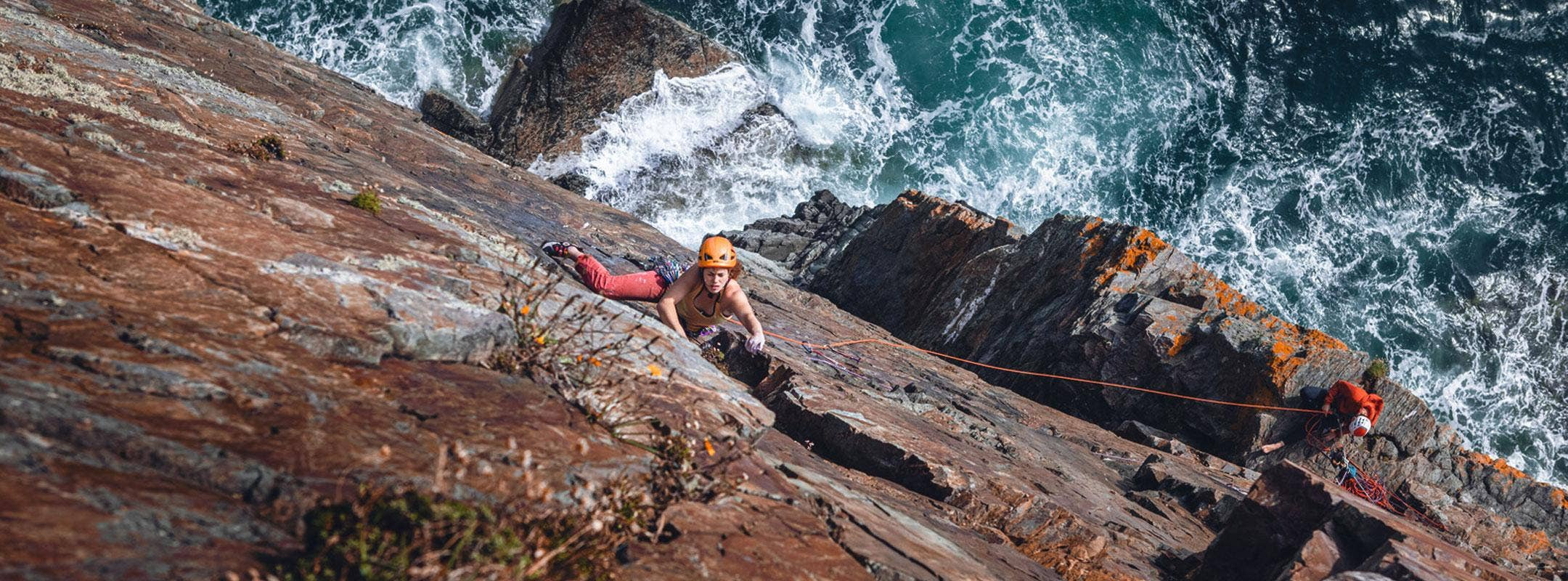 Female climbing up sea cliffs
